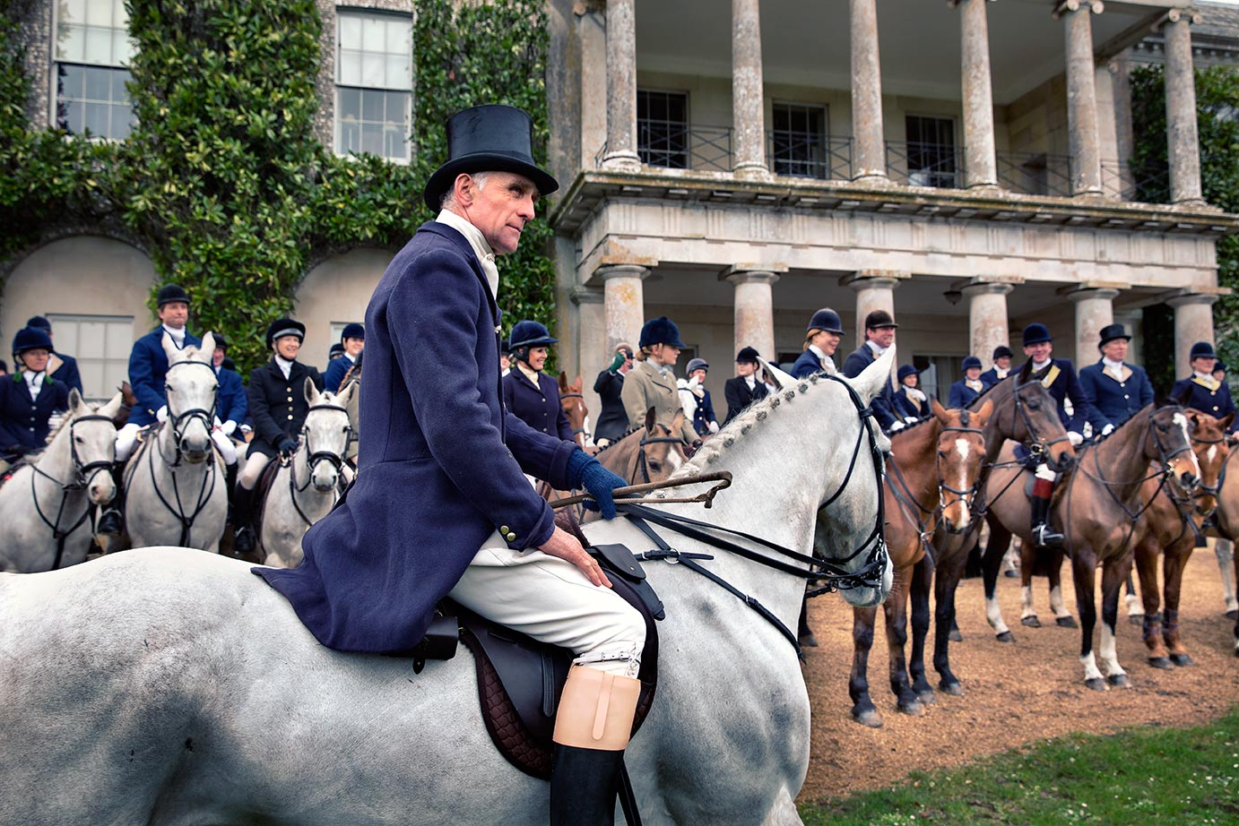 Rider mounted in front of Goodwood house wearing top hat