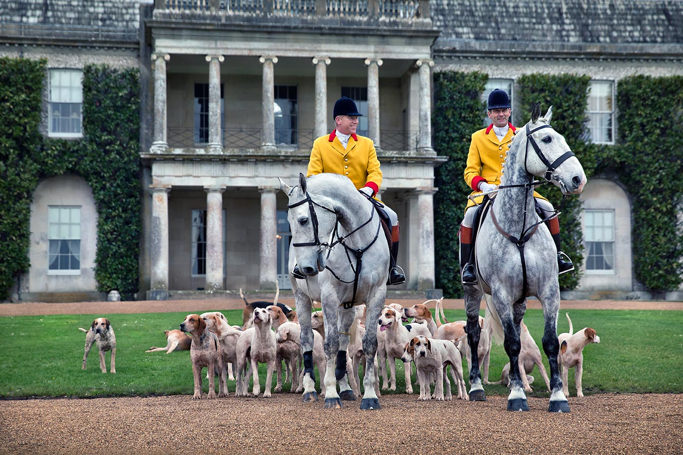 Huntsman and first whip holding the hounds at Goodwood House